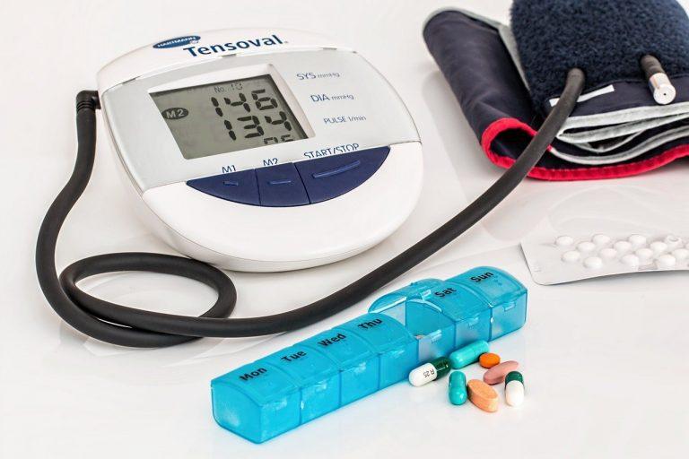 blutdruckmessgerät und Pillen auf einem Tisch