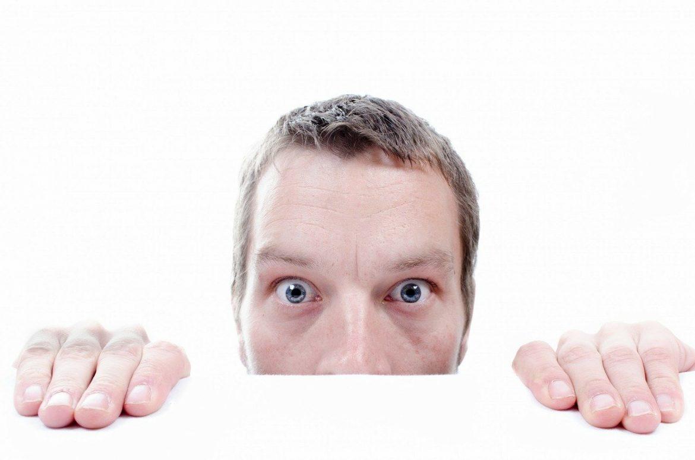 Mann schaut ängstlich über Bürotisch