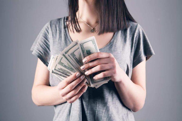 Frau hält ihren Verdienst in der Hand