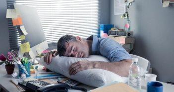 Mann schläft mit Kissen am Schreibtisch