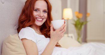 Frau trinkt eine Tasse Kaffee im Bett