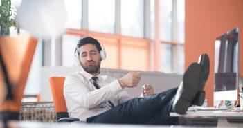 Mann hört Musik an seinem Schreibtisch