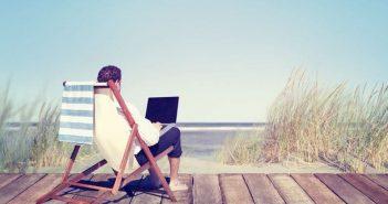 Mann arbeitet im Urlaub mit Laptop
