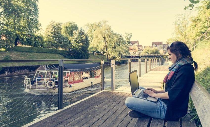 Frau arbeitet mit ihrem Laptop am Kanal