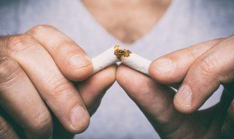 Mann zerbricht Zigarette und will mit dem Rauchen aufhören