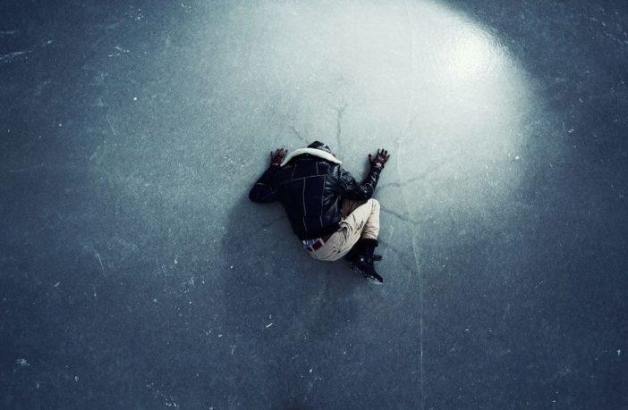 Depressiver Mann liegt im Winter auf dem Eis