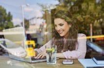 Bloggerin arbeitet am Laptop im Cafe