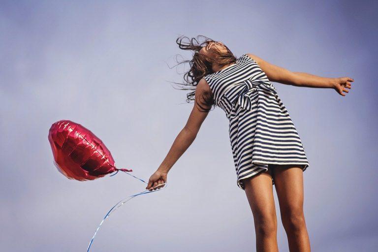 gesunde Frau mit rotem Ballon in der Hand