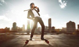 Millenial mit Smartphone auf dem Skateboard