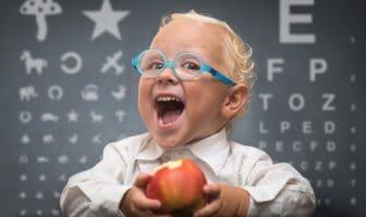 Kluges Kind mit Brille und Apfel vor einer Lerntafel