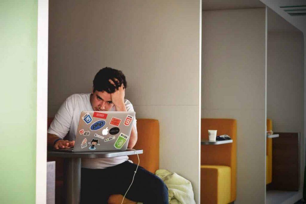 Junger Mann am Laptop hat eine Kreativitätsblockade