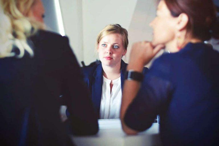 Frau sitzt angespannt und nervös im Bewerbungsgespräch