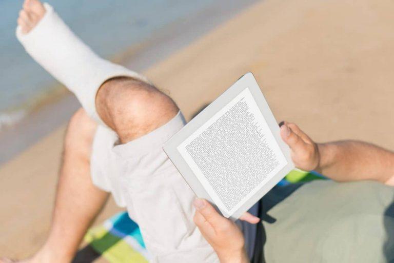 Mann mit Gibsbein liegt im Urlaub am Strand
