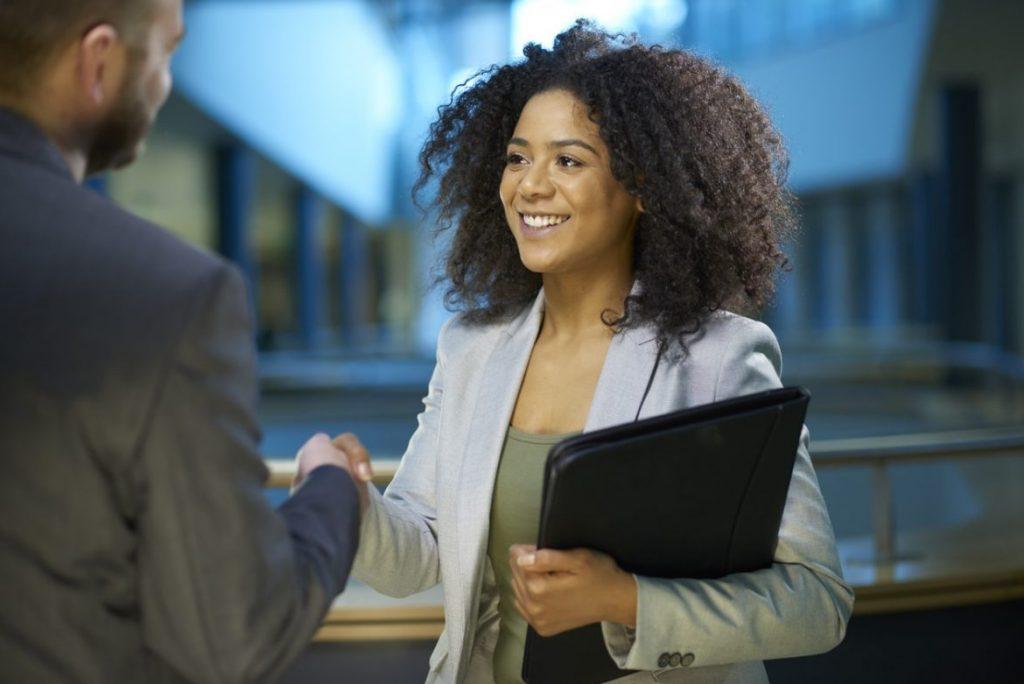 Bewerberin begrüßt Personaler im Vorstellungsgespräch