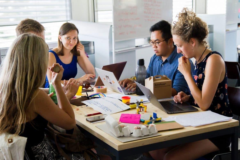 Mitarbeiter diskutieren und arbeiten am Laptop