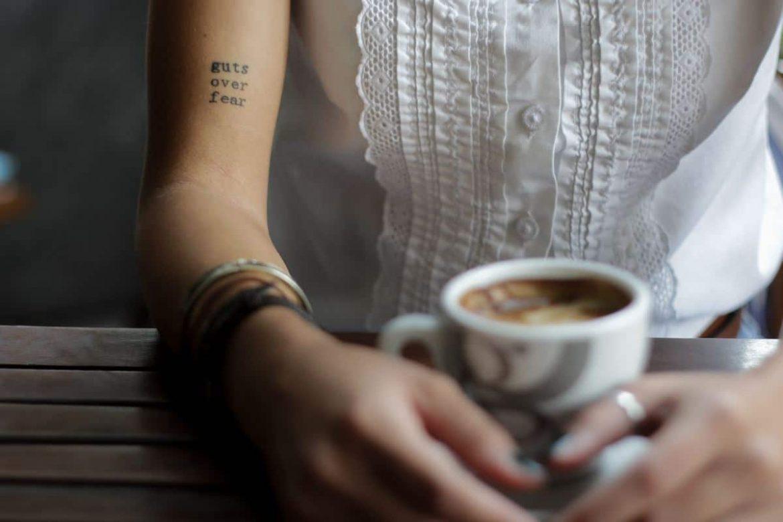 Frau gießt sich Milch in den Kaffeee