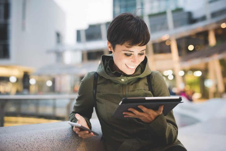 Junge Frau am Tablet freut sich über eine freundliche E-Mail