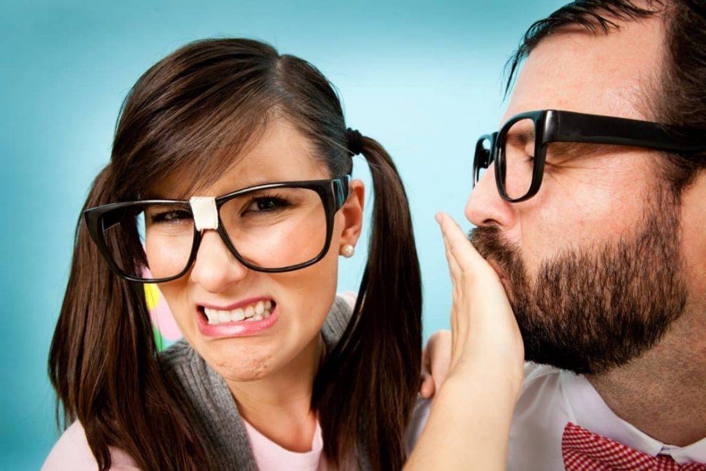 Frau hält einem Kollegen mit üblen Mundgeruch den Mund zu