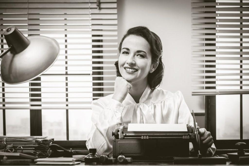 Fröhliche Sekräterin arbeitet an der Schreibmaschine im Büro