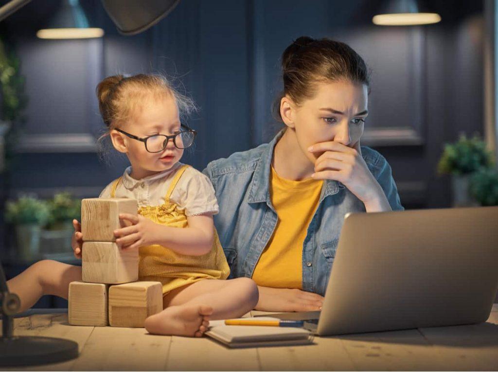 Junge Mutter mit Kind arbeitet im Büro am PC.