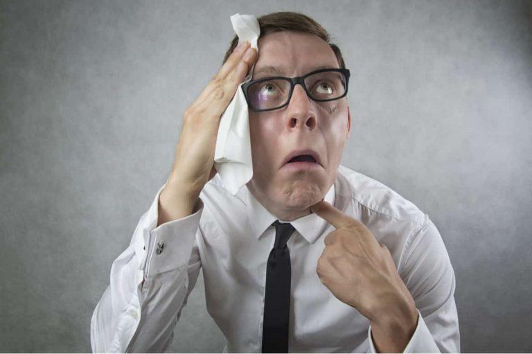 Mann schwitzt bei unerträglicher Hitze im Büro