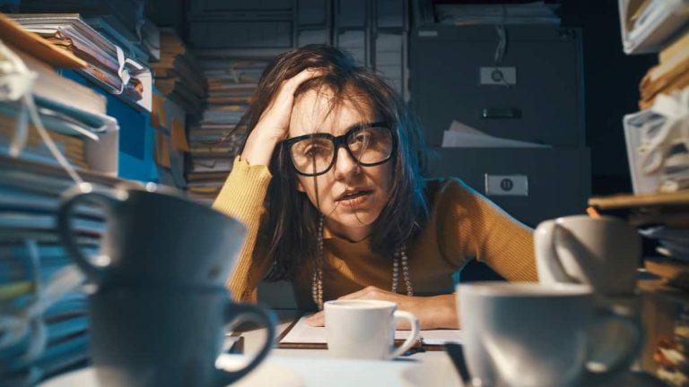 Mit Arbeit überlastete Frau, die am Büroschreibtisch sitzt und Überstunden schiebt