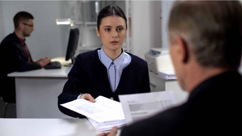 Bewerberin legt ihrem zukünftigen Chef im Rahmen einer Probearbeit ihr Arbeitsergebnis vor