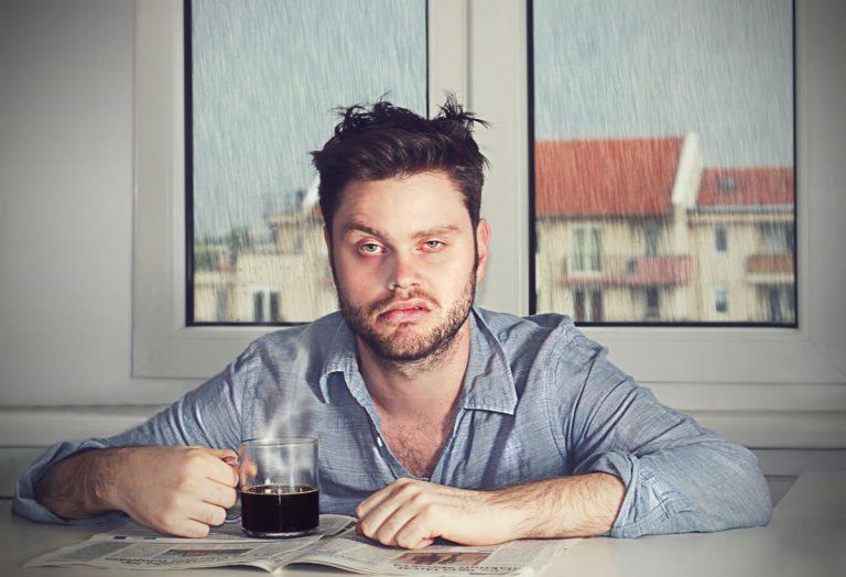 Übermüdeter Arbeitnehmer hat schlecht geschlafen und trinkt Kaffee