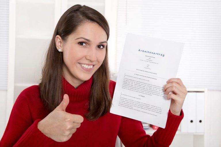 Junge Frau erhält unbefristeten Arbeitsvertrag von ihrem Arbeitgeber