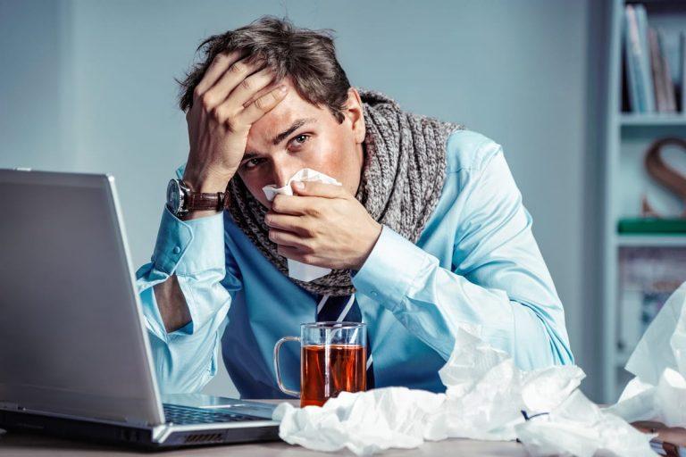 Arbeitnehmer arbeitet trotz starker Erkältung und trinkt eine Tasse Tee am Laptop