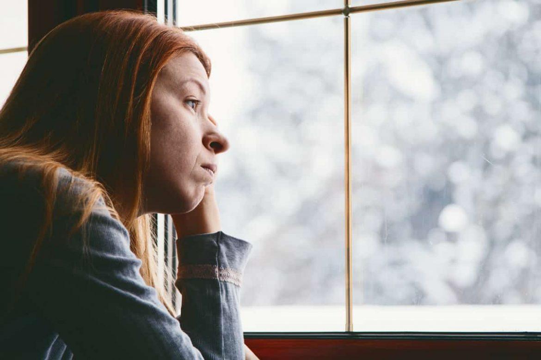 Frau sitzt am Fenster und klagt im Winter über Beschwerden, die auf eine depressive Verstimmung hindeuten